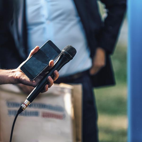 Un redactor cubriendo una noticia con su teléfono móvil